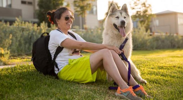 An Arctic Rescue Victoria volunteer sitting with a Siberian Husky